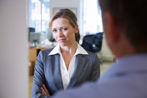 female businesswoman looking uncomfortable talking to a male coworker who is going to call a harassment lawyer newark