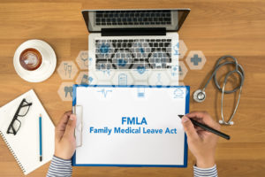 Laptop with person holding a printed sign stating FMLA, Family Medical Leave Act for an FMLA Attorney in Delaware County.