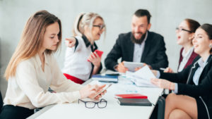 A group of coworkers meeting in conference room with woman being harassed for whistleblowing at work. Speak to a reliable Columbus Workplace Investigation Lawyer.