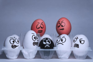 Faces drawn on different colored eggs, reflecting expressions. When you feel harassed at work, meet with the best Lancaster Discrimination Attorney.