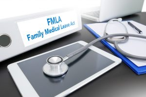 Family Medical Leave Act on a binder with tablet and doctor's stethoscope, if your FMLA benefits have been terminated speak to a skilled Columbus employment attorney.