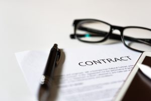 Contract form on table with glasses and pen, for contract review contact a Columbus employment lawyer.