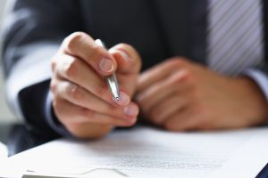 Man pausing to sign paperwork, have a Lancaster separation agreement lawyer review your agreement.