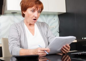 Woman looking shocked at her paycheck, you can count on the Columbus Unpaid Wages Lawyer to fight for your labor laws.