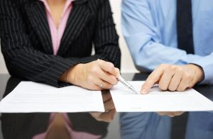 Two people checking paperwork at table, for professional contract negotiations meet with Chillicothe Contract Review Lawyers.