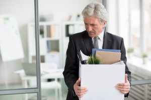 Senior businessman leaving office with box of things, if fired unfairly it is important to meet with Fairfield County Wrongful Termination Attorneys.