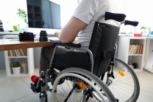 A man in a wheelchair sitting in front of a computer representing how you can benefit from contacting a Zanesville disability discrimination lawyer.