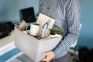 A man carrying a box after being fired representing how a Columbus wrongful termination attorney can help you with your case.
