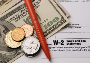 A W-2 document, money and a pen representing how our Columbus wage and hour attorneys can help you get the wages you deserve.