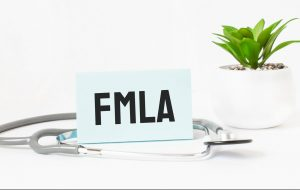 FMLA written on a card with a stethoscope wrapped around it representing how our Newark FMLA can help you obtain the leave you're entitled to.