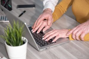Woman typing on laptop with man's hands on top of hers, when experiencing harassment at work turn to Lancaster Sexual Harassment Attorney.